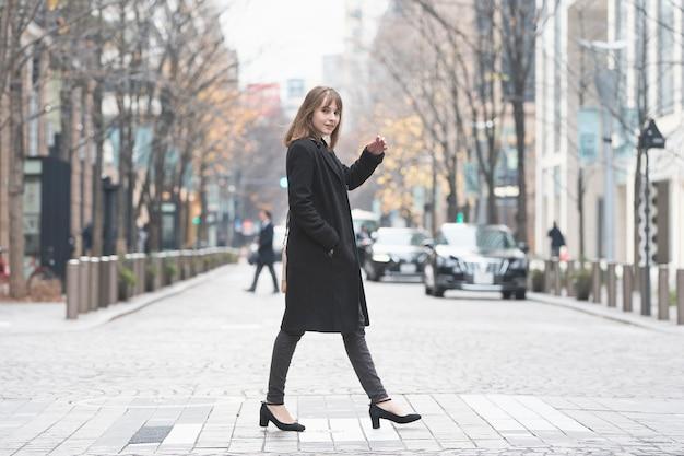 若い女性が丸の内通りを歩く