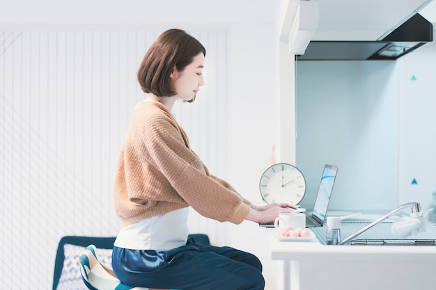 Азиатская молодая женщина, работающая удаленно в домашней комнате