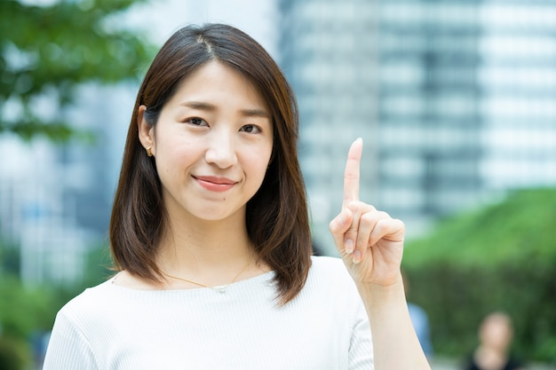 人差し指を上げるビジネス女性