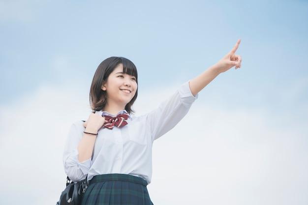 Девушка средней школы, указывая на небо