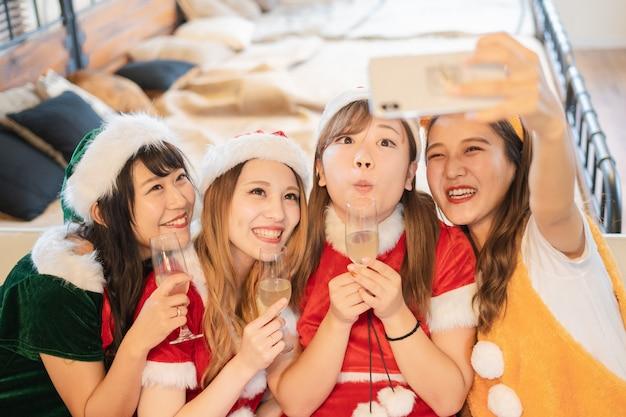 Молодые женщины празднуют рождественскую вечеринку с костюмом санты