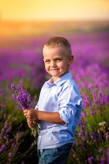 Маленький мальчик играет на красивом поле лаванды. семейный отдых