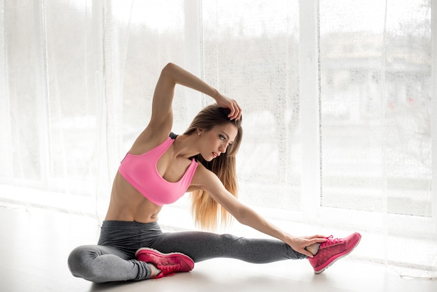 Сексуальная фитнес-спортсменка выполняет разминку перед упражнениями в студии