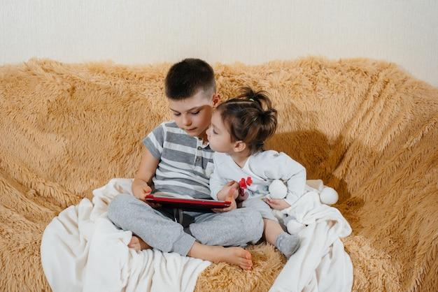 タブレットでソファで遊ぶ兄と妹