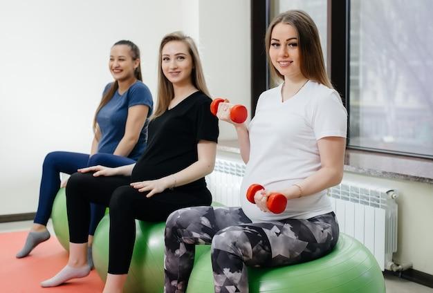 Группа молодых беременных мам занимается пилатесом и мячом в фитнес-клубе. беременная