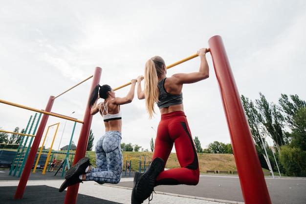 アスレチックでセクシーな女の子がオープンエアのバーを一緒に引き上げます。フィットネス、健康的なライフスタイル