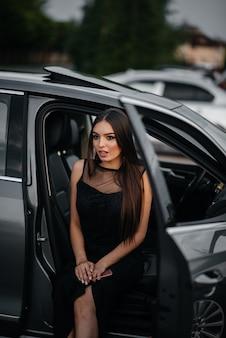 Стильная молодая девушка сидит в машине бизнес-класса в черном платье. деловая мода и стиль