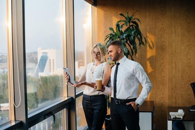 窓口の横でビジネスの問題について話し合うオフィスのスタッフ。企業財務