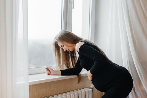 窓際に立っている妊婦の激しい痛み。妊娠