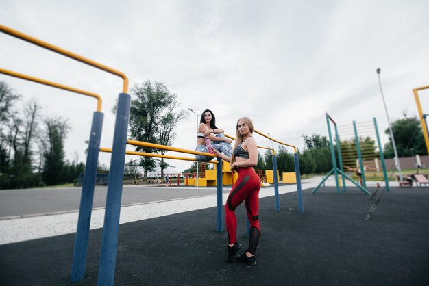 Спортивные, сексуальные девушки занимаются спортом на свежем воздухе. фитнес, здоровый образ жизни