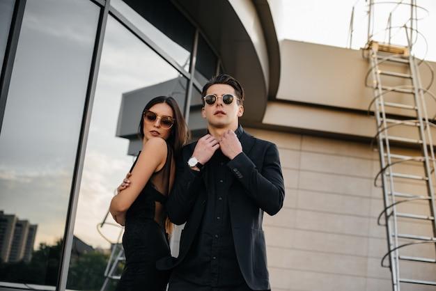 黒い服とメガネを身に着けた美しくスタイリッシュな若者のペアが、日没のオフィスビルを背景に立ちます。ファッションとスタイル