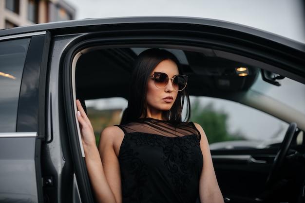 黒のドレスでビジネスクラスの車に座っているスタイリッシュな若い女の子。ビジネスファッションとスタイル