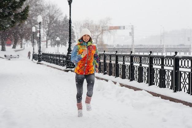 Красивая молодая девушка бегает в морозный и снежный день. спорт, здоровый образ жизни