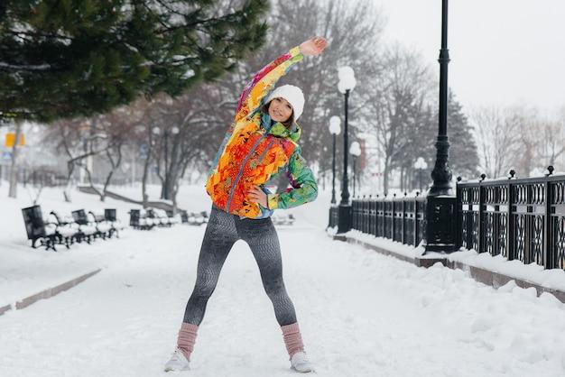 Молодая спортивная девушка занимается спортом в морозный и снежный день. фитнес, бег