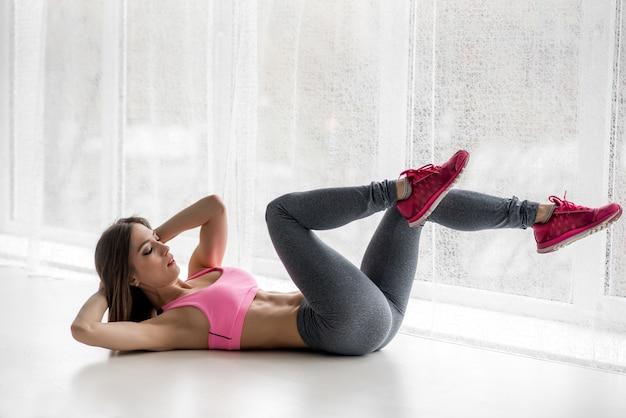 Сексуальная фитнес спортсменка выполняет упражнения на мышцы пресса в студии. бодибилдинг