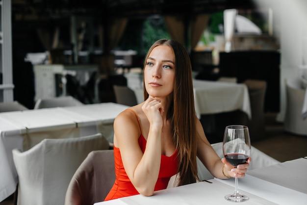 Красивая молодая девушка сидит и пьет вино на веранде красивого дома. праздничный день.