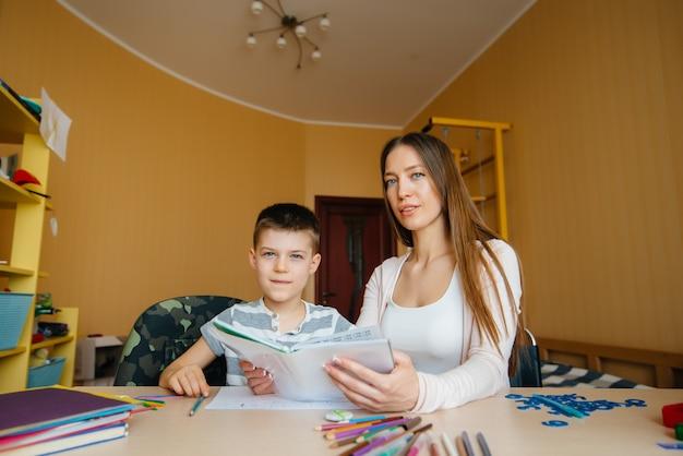 若い母親が息子と家で宿題をしている。保護者とトレーニング