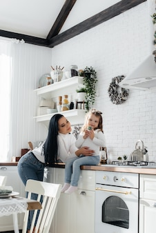 ママとリトルドーターはキッチンで料理をして遊んでいます。家族、幸せ。