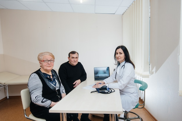 医療センターでかかりつけの医師の診察を受ける高齢者のカップル。医学とヘルスケア