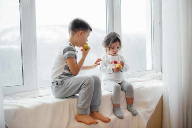 兄と妹は窓辺に座って、リンゴを食べたり遊んだりしています。幸福