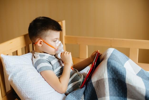 少年は、肺の吸入中にタブレットで遊ぶ。薬とケア