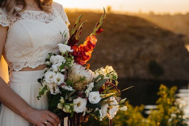 Потрясающе красивый и стильный свадебный букет держит невесту крупным планом. флористический