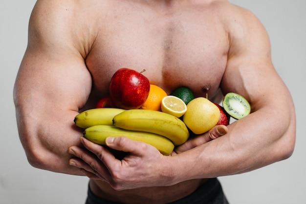 明るい果物と白い壁でポーズスポーティなセクシーな男。ダイエット。健康的なダイエット