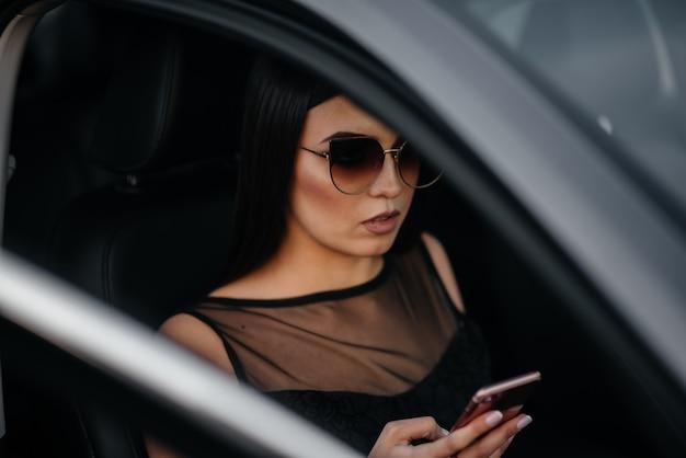 Стильная молодая девушка сидит в машине бизнес-класса в черном платье и разговаривает по телефону. деловая мода и стиль
