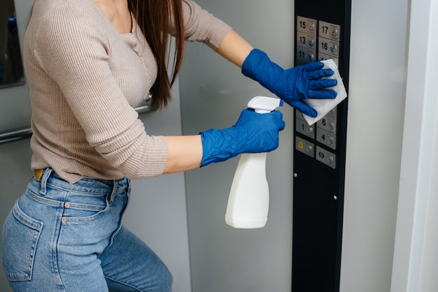 Молодая женщина дезинфицирует и чистит ключи в лифте во время глобальной пандемии. останься дома