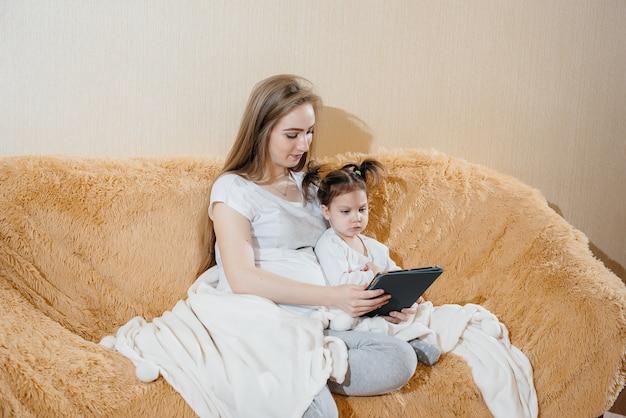 妊娠中の母親が小さな娘と一緒にソファに座って、ガジェットで遊んでいます