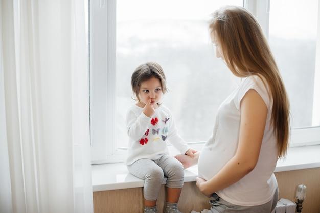 Беременная мать стоит возле окна со своей маленькой дочерью