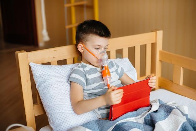 少年は、肺の吸入処置中にタブレットで遊ぶ。薬とケア