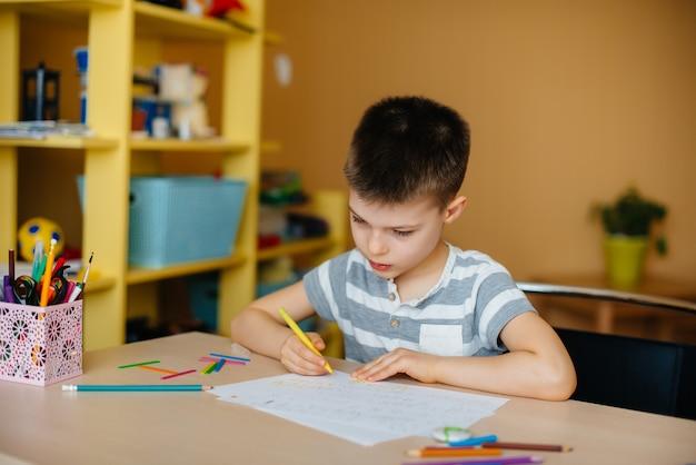 Мальчик школьного возраста делает домашнее задание дома. обучение в школе