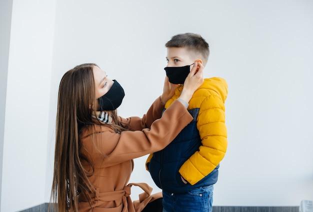 隔離中、子供を持つ母親が仮面に立っています。パンデミック、コロナウイルス