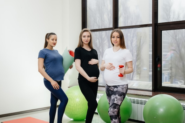 若い妊娠中の女の子のグループは、ヨガをし、屋内で社交します。健康的な生活様式
