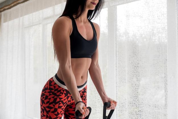 明るい背景にスタジオでフィットネスを行う運動の若い女の子。フィットネス、健康的なライフスタイル