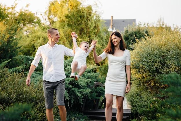 Счастливая семья с сыном, прогулки в парке на закате. счастье. люблю