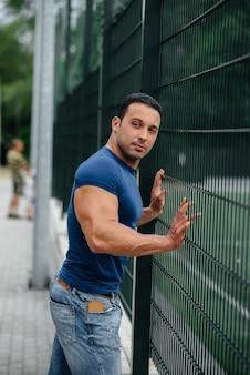 スポーツ男はスポーツフィールドの近くに立っています。ボディービル