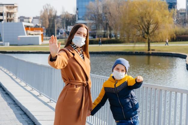 検疫とパンデミックの最中、晴れた日に若い家族が歩いて新鮮な空気を吸い込みます。人々の顔のマスク