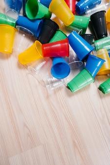 色とりどりのプラスチック製のコップの大きな山が空きスペースのある床に散らばっています。し尿による環境汚染