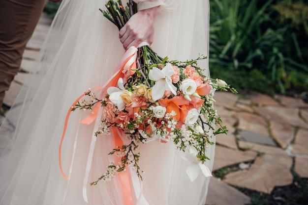 美しく洗練されたウェディングブーケのクローズアップは、花嫁を手に持っています。ウェディングブーケ