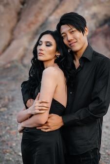 黒い革の服を着た愛のアジアカップルが木の中で自然の中を歩きます。スタイル、ファッション、愛