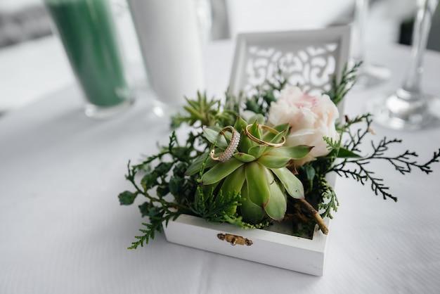 花嫁の集まりの間に、美しいボックスに結婚指輪をクローズアップ。アクセサリー