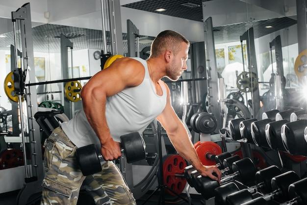 若い運動男はジムでフィットネスに従事しています。フィットネス、ボディービル
