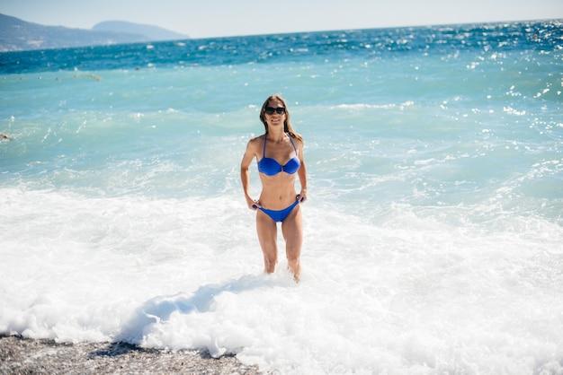 Молодая сексуальная девушка отдыхает на берегу океана в солнечный день. отдых, туризм