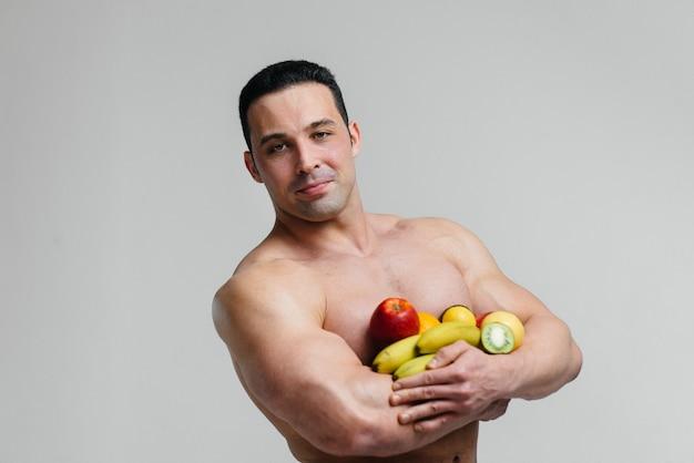明るい果物と白い背景でポーズスポーティなセクシーな男。ダイエット。健康的なダイエット
