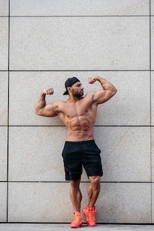 Сексуальный спортсмен стоит топлесс возле стены. фитнес, бодибилдинг
