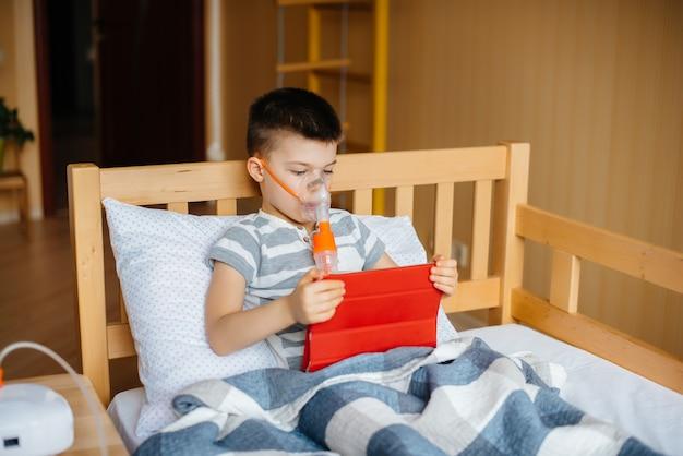 少年は、肺の吸入処置中にタブレットで遊ぶ。薬とケア。