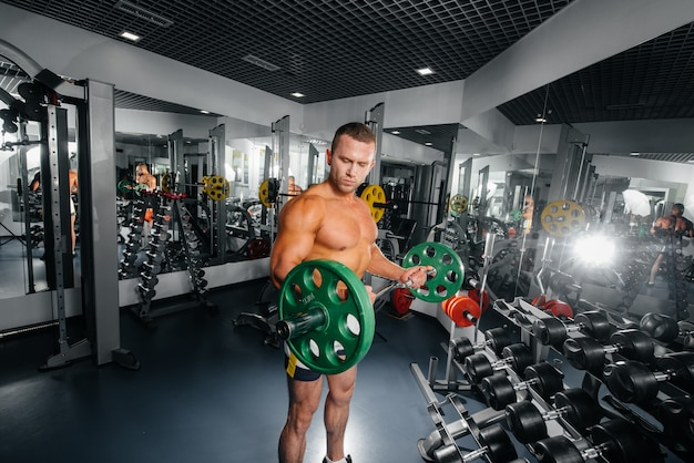 若い運動男はジムでフィットネスに従事しています。フィットネス、ボディービル。