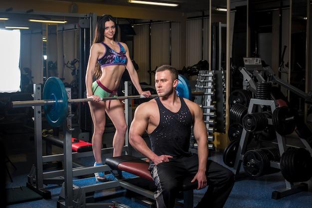 Пара молодых спортсменов занимается в спортзале, помогая друг другу. фитнес, бодибилдинг.